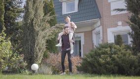 Młoda przystojna ojciec pozycja przed dużym domem z córki obsiadaniem na jego brać na swoje barki Dziecko trzyma małym zdjęcie wideo