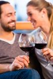Młoda przystojna para pije czerwone wino Zdjęcia Royalty Free