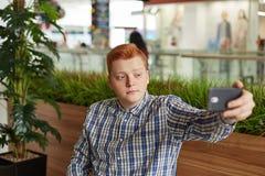 Młoda przystojna samiec z czerwonym włosy ma naturalnego wyrażenie w kawiarni podczas gdy robić selfie na jego smartphone odizolo obraz royalty free