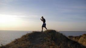Młoda pugilist samiec ćwiczy boksujący cios przed zacierać się na wzgórzu blisko rzeki zdjęcie wideo