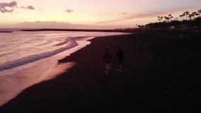 M?oda rodzina chodzi wzd?u? czarnej pla?y na oceanie przy zmierzchem, widok od trutnia Tenerife, Hiszpania zbiory wideo