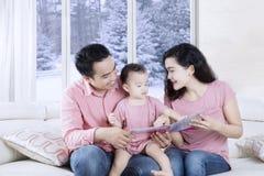 Młoda rodzina czyta storybook na leżance fotografia stock
