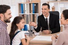Młoda rodzina kupuje nieruchomość w biurze pośrednik handlu nieruchomościami Pośrednik handlu nieruchomościami pomocy zakupu młod Obrazy Stock