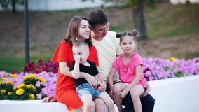 Młoda rodzina siedzi w parku obok pięknych kwiatów, która składać się z 4 ludzie, zbiory