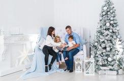 Młoda rodzina składająca się z czterech osób blisko dekorował Bożenarodzeniowej jedliny w białym pokoju fotografia stock