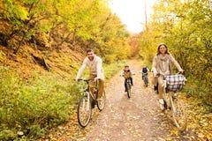 Młoda rodzina w ciepłym odzieżowym kolarstwie w jesień parku fotografia stock