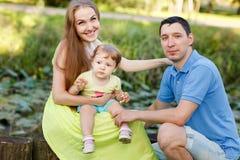 Młoda rodzina w parku wśród krzaków Obrazy Royalty Free