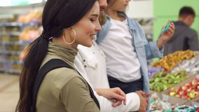 Młoda rodzina z śliczną małą córką wybiera cukierek w dużym ciasto sklepie zbiory wideo