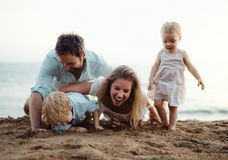 Młoda rodzina z berbeci dziećmi bawić się z piaskiem na plaży na wakacje letni obrazy stock