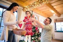 Młoda rodzina z daugter przy choinką w domu Zdjęcia Stock