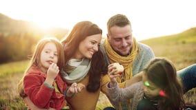 Młoda rodzina z dwa małymi dziećmi siedzi na trawie w jesieni naturze zbiory