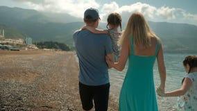 Młoda rodzina z dziećmi chodzi wzdłuż brzeg na letnim dniu zbiory wideo