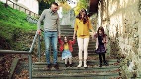 M?oda rodzina z dzie?mi na schodkach outdoors w miasteczku w jesieni zbiory