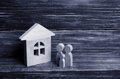Młoda rodzina z dziećmi stoi blisko drewnianego domu Pojęcie silna rodzina kontynuacja rodzina Zdjęcia Stock
