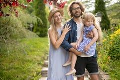 Młoda rodzina z koszem po tym jak pykniczni odprowadzenie puszka schodki outside w zieleń parku obrazy stock