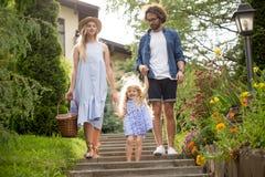 Młoda rodzina z koszem po tym jak pykniczni odprowadzenie puszka schodki outside w zieleń parku obrazy royalty free