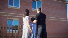 Młoda rodzina z syna trwanie outside nowy dom i obejmowanie zbiory