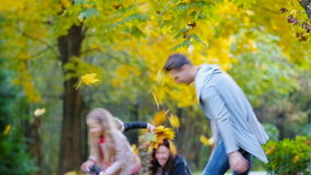 Młoda rodzina zabawy miotania liście wokoło na jesień dniu outdoors zbiory wideo