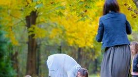 Młoda rodzina zabawy miotania liście wokoło na jesień dniu outdoors zdjęcie wideo