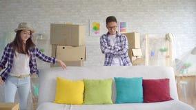 Młoda rodzinna Azjatycka para ruszał się w nowego mieszkanie, one usuwa ochronnego celofan od kanapy zdjęcie wideo