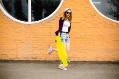 Młoda rozochocona dziewczyna pozuje z żółty deskorolka przeciw pomarańcze ścianie fotografia stock