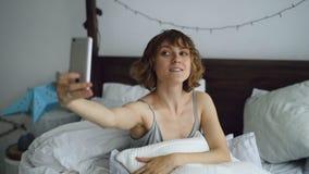 Młoda rozochocona kobieta bierze selfie portret używać smartphone obsiadanie w łóżku wewnątrz w domu Zdjęcie Royalty Free
