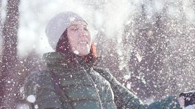 Młoda rozochocona kobieta podrzuca puszystego śnieg w parku