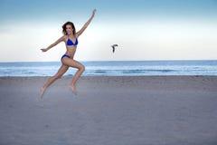 Młoda rozochocona kobieta w bikini doskakiwaniu na plaży Fotografia Stock