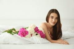 Młoda rozochocona kobieta z pięknym bukietem peonie kłama na łóżku Zdjęcie Royalty Free