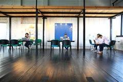 Młoda rozpoczęcie grupa pracuje w nowożytnym biurze Otwarta przestrzeń, laptopy i papierkowa robota, obraz royalty free
