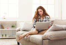 Młoda rudzielec dziewczyna z laptopu obsiadaniem na beżowej leżance Zdjęcia Royalty Free