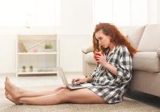 Młoda rudzielec dziewczyna z laptopu obsiadaniem na podłoga Obrazy Stock
