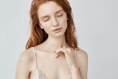 Młoda rudzielec dziewczyna z piegami pozuje z zamkniętymi oczami zdjęcia stock