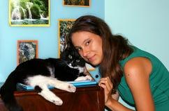 Młoda 20s dziewczyna i czarny i biały kot patrzeje kamerę, on Obraz Royalty Free