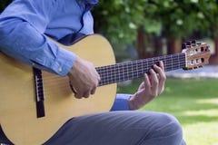 Młoda samiec bawić się klasyczną gitarę outside Zdjęcia Royalty Free
