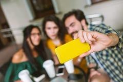 Młoda samiec i dwa żeński bierze selfie w kawiarni outdoors Fotografia Stock