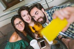 Młoda samiec i dwa żeński bierze selfie w kawiarni outdoors Zdjęcia Stock