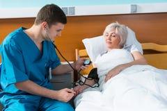 Młoda samiec lekarka w mundurze z fonendoskopem jest mierzyć Obraz Stock