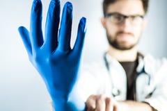 Młoda samiec lekarka z błękitną rękawiczką obrazy stock