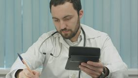 Młoda samiec lekarka z kalkulatorem robi obliczeniom i robi notatkom zdjęcie royalty free