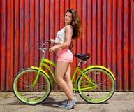 Młoda seksowna brunetki dziewczyna z długie włosy trwanie pobliskim bicyklem fotografia stock