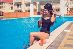 Młoda seksowna dziewczyna przy pływackim basenem Pije koktajl zdjęcia royalty free