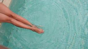 Młoda seksowna kobieta w białym swimsuit obsiadaniu basenem z błękitne wody zbiory wideo
