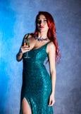 Młoda seksowna kobieta z dużymi boobs w błękitnym eleganckiej sukni mienia wineglass z szampanem obraz stock