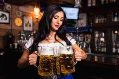Młoda seksowna Oktoberfest kelnerka, będący ubranym tradycyjną Bawarską suknię przy barem, słuzyć duzi piwni kubki Fotografia Stock