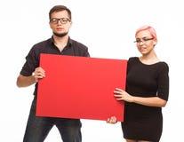 Młoda seksowna para pokazuje prezentację wskazuje plakat Fotografia Royalty Free