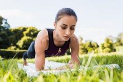 młoda skoncentrowana kobieta robi desce na trawy łące obraz royalty free