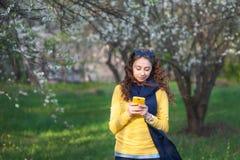 Młoda smilling kobiety pozycja w kwitnącym ogródzie i pisze na telefonie komórkowym cherry kwitn?ca pi?kna portret kobiety obraz royalty free