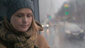 Młoda smutna kobieta w autobusie na niedźwięcznym deszczowym dniu zbiory