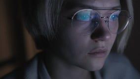 Młoda smutna kobieta w szkłach podrzuca wiadomości karmy komputer w ciemnym pokoju wewnątrz zbiory